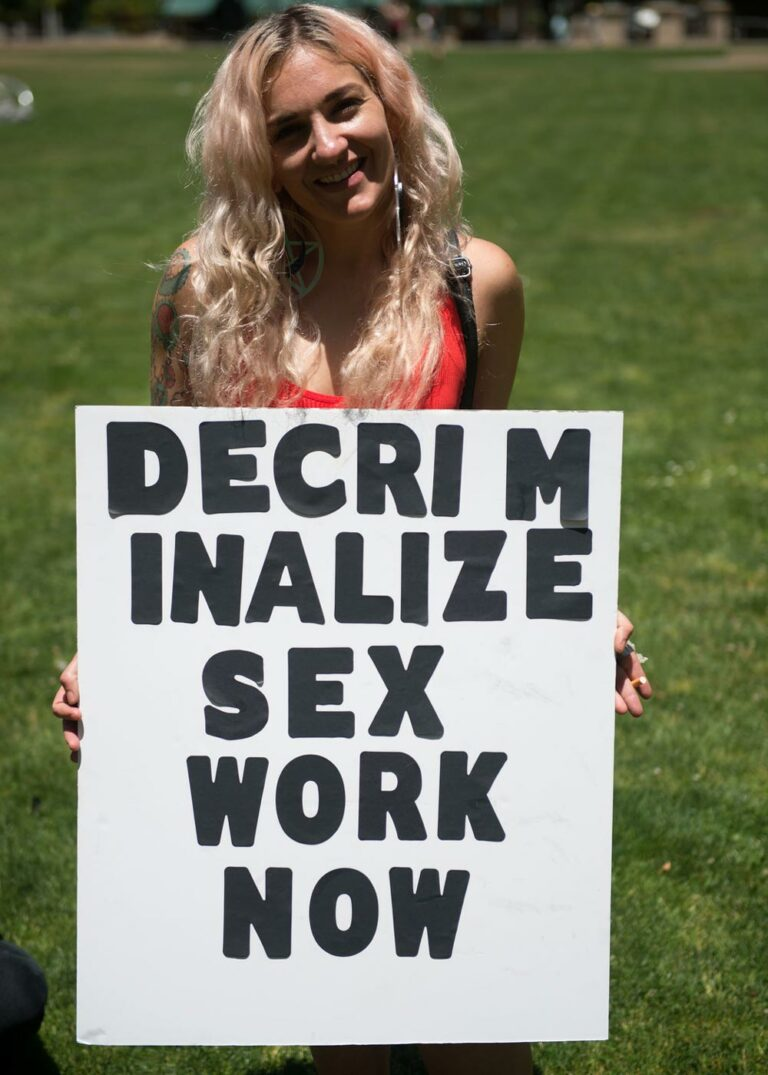 person smiling and holding a sign that says, decriminalize sex work now